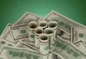 Triangle of dollar bills on green background — Stock Photo