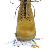 Yellow shoes on cigarettes and drugs — Stock Photo