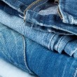 Stack of jeans in different colors - Stock Photo