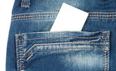 Back pocket of blue jeans with a white card — Stock Photo