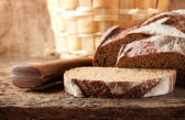 Sliced brown bread with knife — Stock Photo