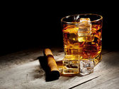 Glass of aged whiskey with cigar and ice cubes — Foto de Stock