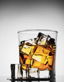 Glass of whiskey with ice melted — Stock Photo
