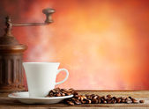 White cup with coffee beans and grinder — Stock Photo