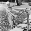 Young woman climbing up the ladder of a swimming pool — Stockfoto #12296278