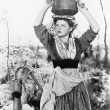 Young woman with water bucket on her head next to a well — Stock Photo #12299536