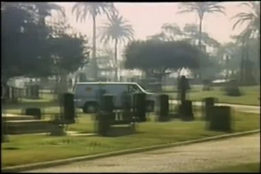 Wide shot van driving through cemetery — Stockvideo