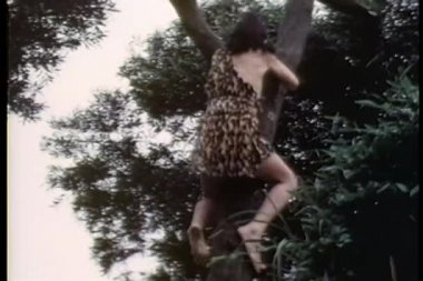 Low angle view child climbing up tree to play with monkey — Stock Video