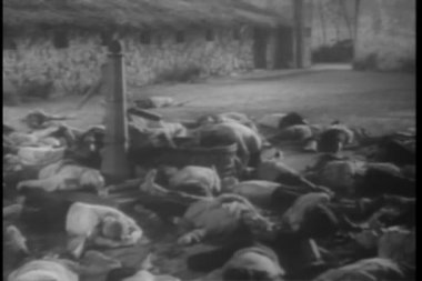 Historical reenactment World War II dead prisoners laying on ground by water pump — Stock Video