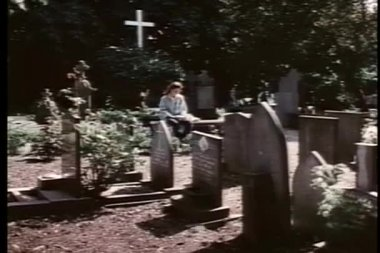Mulher sentada sozinha no cemitério lendo livro — Vídeo Stock
