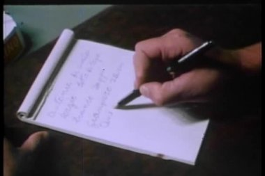 Man sitting at desk writing slowly on paper — Stock Video