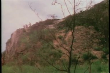 Wide shot men holding spears standing on a cliff — Stock Video