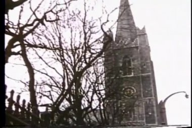 Panning from church steeple to busy village street — Stock Video