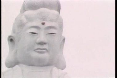 Establishing shot of giant Asian statue and pagoda — Vídeo Stock