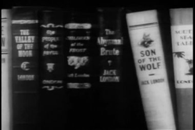 Panning shelf filled with books written by Jack London — Stock Video