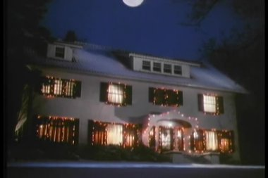 Establishing shot of full moon hovering over house decorated in Christmas lights — Stock Video
