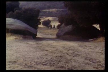 Män på häst galopperar genom bergen — Stockvideo