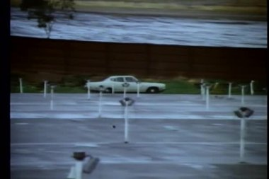 1970s car driving along empty drive-in — Stock Video
