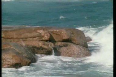 Wide shot of waves crashing against rocks — Stock Video