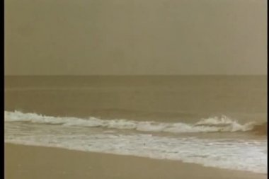 Wide shot small waves crashing on the beach — Wideo stockowe