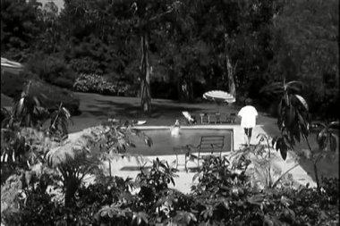 Hombre de tiro largo buceo en la piscina y piscina — Vídeo de stock