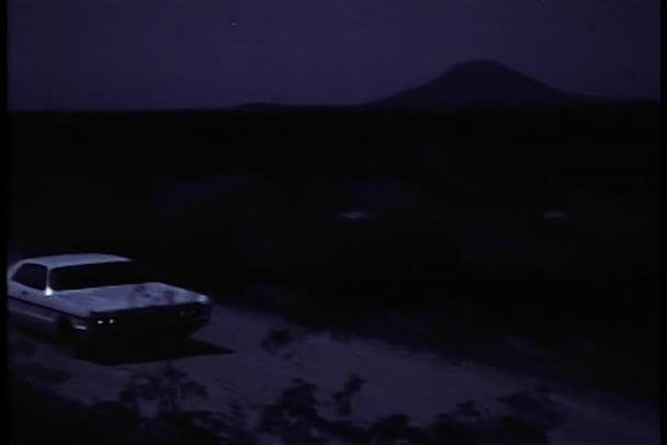 Voiture sur chemin de terre faisant demi-tour dans la nuit — Vidéo