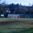 Stock Video: Wide shot of high school football team practicing
