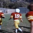 High school football team and coach running across field — Stock Video #26643203