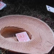 Close-up of throwing playing cards into straw hat on grass — Vidéo