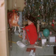 Stock Video: Little boy unwrapping presents under Christmas tree