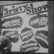 Rear view of worker putting up billboard for variety show — Wideo stockowe