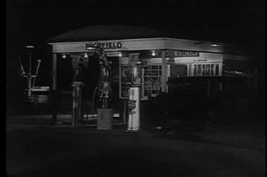 Wide shot ot 1930s car entering gas station at night — Stock Video
