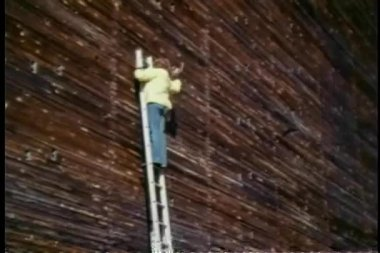 Man on a stepladder hammering into wall — Vídeo Stock