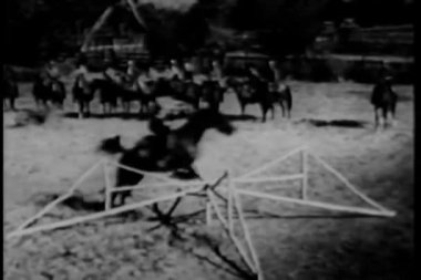 Cowboys on horseback jumping fence in a show ring — Stock Video