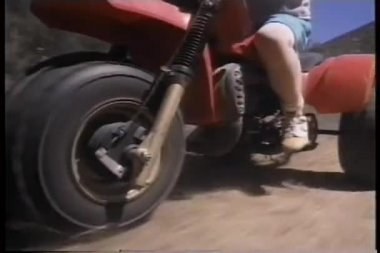 Low angle view of boy riding ATC bike on dirt road — Vídeo Stock
