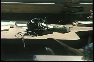 Man's feet up near rotary phone and lit cigarette in ashtray — Stock Video