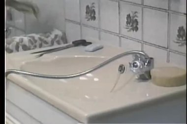Water flowing from bathroom faucet hose directly into camera — Stock Video