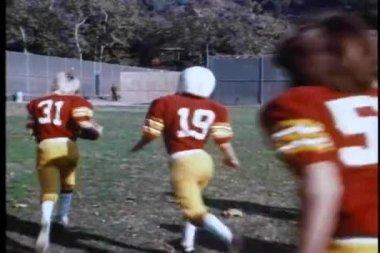 High school fotbollslag och coach löper över fältet — Stockvideo