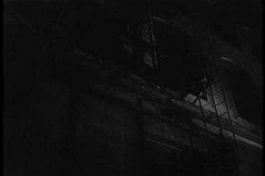 Vista posteriore dell'uomo in movimento verso il basso sulla scala antincendio di notte — Video Stock