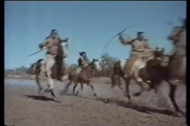 American Indians on horseback galloping along river — Stok video