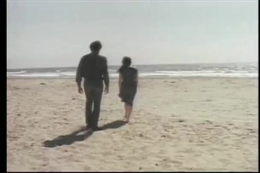Vista trasera del hombre y la mujer caminando hacia el océano — Vídeo de stock