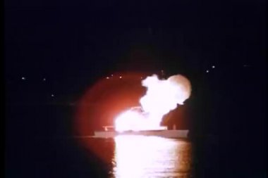 Wide shot of yacht exploding at night in port — Stock Video