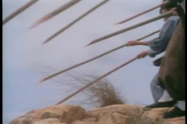 Men throwing lances from cliff — Stock Video