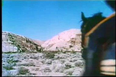 Rear view of cavalry officer and prisoner on horseback galloping through mountain terrain — Stock Video