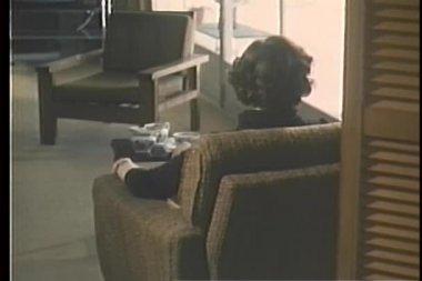 Vue arrière de la femme assise dans le fauteuil perdu dans ses pensées — Vidéo