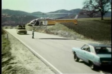 Man coordinating stunt cars and helicopter on location — ストックビデオ