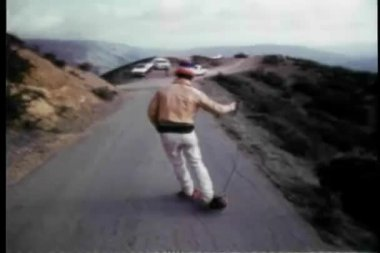 Rear view of a man skateboarding on mountain road — Stock Video