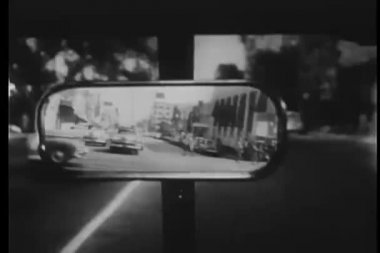 Close-up of rear-view car mirror of two cars following on street of Los Angeles, California, USA — Stock Video