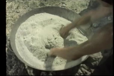 Hands withstanding pain from heated sand in pan — Стоковое видео