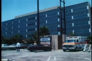 Wide shot of walking in front of hospital — Stockvideo